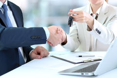 Saleswoman handing over the keys for a new car to a young bu Stock Image