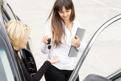 Saleswoman handing over the keys to a new car. To a blond women sitting in the drivers seat Royalty Free Stock Photo