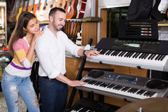 Saleswoman helping man to select synthesisers Stock Photos