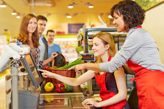 Saleswoman helping woman at. Elderly saleswoman helping young women at supermarket checkout stock images
