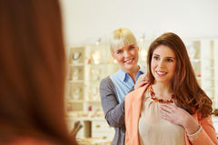 Saleswoman helping woman fitting Royalty Free Stock Photos