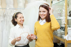 Saleswoman helps bride chooses bridal accessories Stock Images