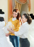 Saleswoman helps bride chooses bridal gown Royalty Free Stock Photos