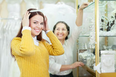 Saleswoman helps bride chooses bridal wreath Royalty Free Stock Image