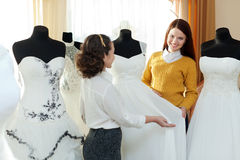 Saleswoman helps girl chooses  bridal outfit Stock Images