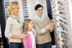 Saleswoman helps to child to choose frames for eyeglasses royalty free stock photography