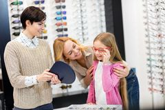 Saleswoman hold mirror while child try frames for eyeglasses royalty free stock images