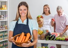 Saleswoman Holding Carrot Basket At Supermarket Stock Photos