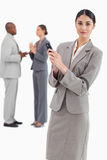 Saleswoman holding cellphone with colleagues behind her Stock Photos