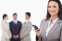 Saleswoman holding cellphone with team behind her Royalty Free Stock Photo