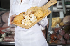 Saleswoman Holding Cutting Board With Assorted Cheese Royalty Free Stock Image