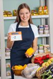 Saleswoman Holding Pricetag And Bellpepper In Royalty Free Stock Photography