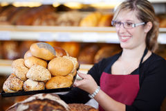 Saleswoman holding a tray of bread rolls Royalty Free Stock Photo
