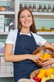 Saleswoman Holding Vegetable Basket In Grocery Royalty Free Stock Photography