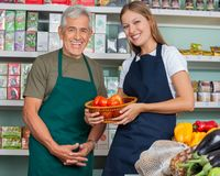 Saleswoman Holding Vegetable Basket With Male Royalty Free Stock Photography