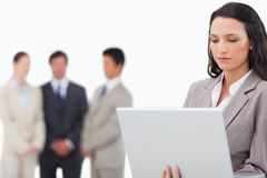 Saleswoman with laptop and colleagues behind her Stock Image