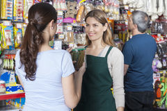 Saleswoman Looking At Customer Holding Dog Food Jar. Smiling saleswoman looking at female customer holding dog food jar in store stock image