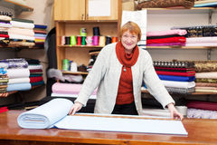 Saleswoman measures the fabric. In a fabric shop Royalty Free Stock Image