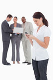 Saleswoman with mobile phone and colleagues behind her Stock Photography