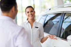 Saleswoman new car customer. Attractive saleswoman showing new car to a customer in showroom stock image