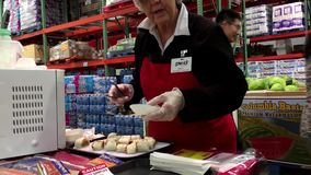 Saleswoman offering Mexican burritos food samples to customers stock video footage