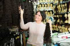 Saleswoman offering wigs Stock Images