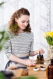 Saleswoman organizing natural oils. In the shop with organic creams stock photography