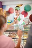 Saleswoman in pastry store gives ice cream to girl stock photos