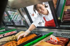 Saleswoman Picking Meat Displayed In Cabinet. Portrait of smiling saleswoman picking meat displayed in cabinet at butcher's shop Royalty Free Stock Photography
