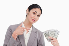 Saleswoman pointing at bank notes in her hand Royalty Free Stock Photos