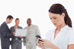 Saleswoman reading text message with colleagues behind her Royalty Free Stock Photo