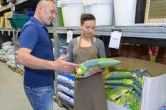 Saleswoman recommending man fertilizer for orchid plant in nursery. Saleswoman recommending men a fertilizer for orchid plant in nursery stock images