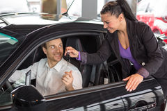 Saleswoman selling a car to happy customer Royalty Free Stock Photography