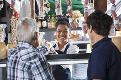 Saleswoman Selling Cheese To Male Customers At Shop Royalty Free Stock Photo