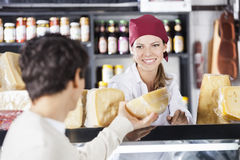 Saleswoman Selling Cheese To Man In Grocery Store. Smiling young saleswoman selling cheese to men in grocery store royalty free stock photo