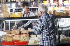 Saleswoman Selling Cheese To Senior Man At Shop. Happy young saleswoman selling cheese to senior men at shop royalty free stock photos