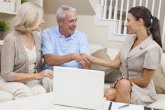 Saleswoman Shaking Hands With Senior Couple. A saleswoman with laptop computer shaking hands with a senior couple at home stock photos