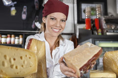 Saleswoman Showing Cheese In Grocery Shop. Portrait of young saleswoman showing cheese in grocery shop royalty free stock photo