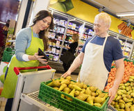Saleswoman Showing Digital Tablet To Colleague In Fruits Departm Royalty Free Stock Photos