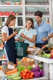 Saleswoman Showing Vegetable Packet To Couple. Young saleswoman showing vegetable packet to couple in supermarket Stock Photos