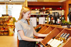 Saleswoman in supermarket organizing wine department. Young saleswoman in supermarket organizing bottles in wine department royalty free stock photography