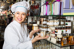 Saleswoman with sweets in jars Stock Images
