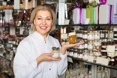 Saleswoman with sweets in jars Royalty Free Stock Image