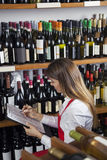 Saleswoman Taking Inventory In Wine Shop. Mid adult saleswoman taking inventory in wine shop Royalty Free Stock Photography