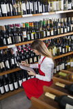 Saleswoman Taking Inventory In Wine Store. Mid adult saleswoman taking inventory in wine store Stock Images