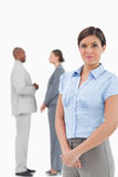Saleswoman with talking associates behind her Royalty Free Stock Photos