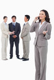 Saleswoman talking on cellphone with colleagues behind her Royalty Free Stock Photos