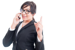 Saleswoman talking on the phone and making wait gesture Royalty Free Stock Photos