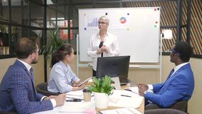 Saleswoman talks with multiethnic team about startup import project in lighting room. stock footage