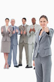Saleswoman with thumb up and her team behind her Royalty Free Stock Photography